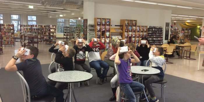 Kinder mit Virtual-Reality-Brillen in einer Bibliothek
