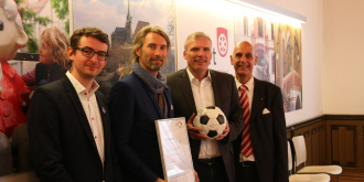 Sven Söderberg (Spirit of Football e. V.), Andrew Aris (Spirit of Football e. V.), Oberbürgermeister Andreas Bausewein mit Ball in den Händen und Friedrich Hermann (KoWo-Geschäftsführer)