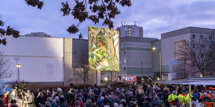 Zahlreiche Menschen stehen vor einem beleuchteten Wandmosaik