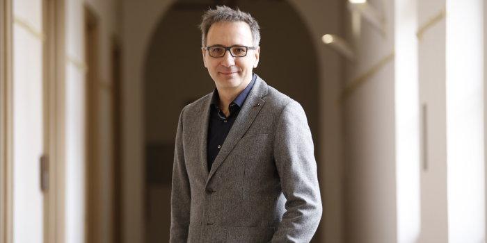 Ein Mann mit grauen Haaren, Brille und grauer Jacke steht in einem Gang.